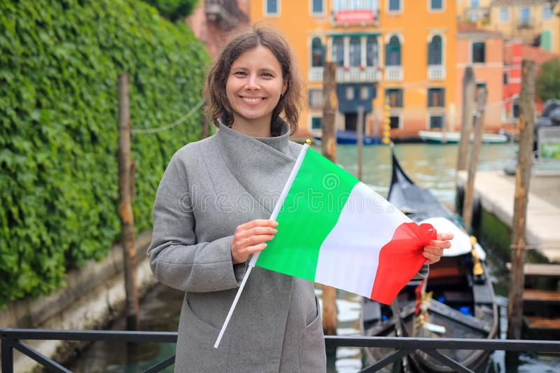 Woman in Venice with italian flag in hands. Girl on gondola in canal background. Happy tourist in Venezia, Italy. Travel Europe stock images