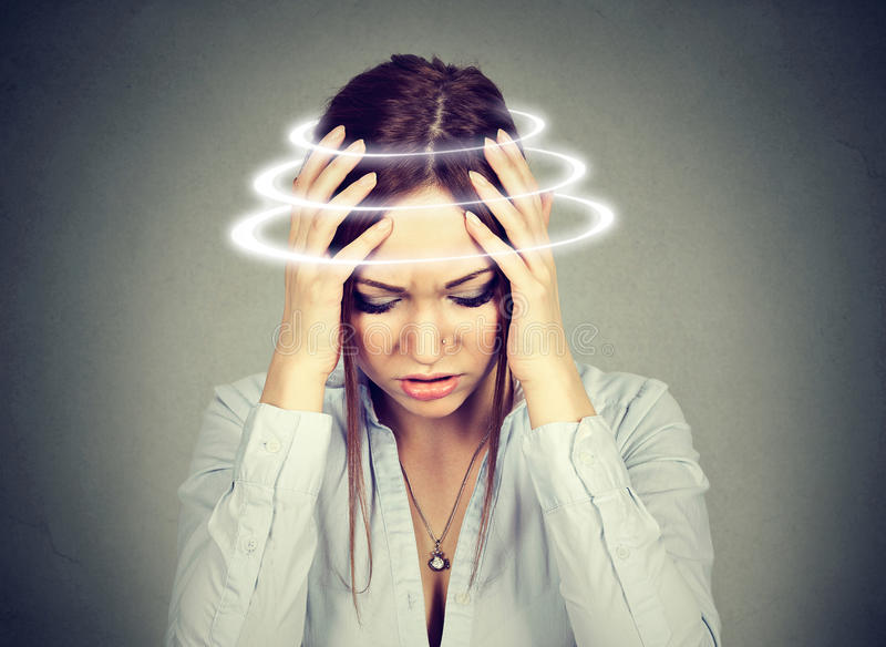 Woman with vertigo. Young female patient suffering from dizziness stock image