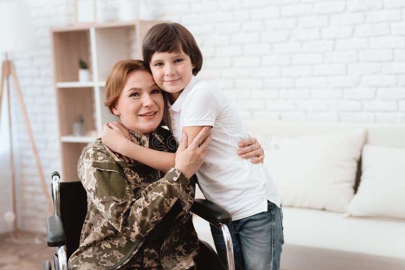 Woman veteran in wheelchair returned home. Son hugs mom in wheelchair. royalty free stock photos