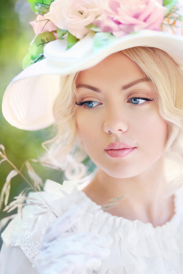 Woman in victorian age. Portrait of beautiful woman in victorian age dress and fancy hat with flowers stock photography