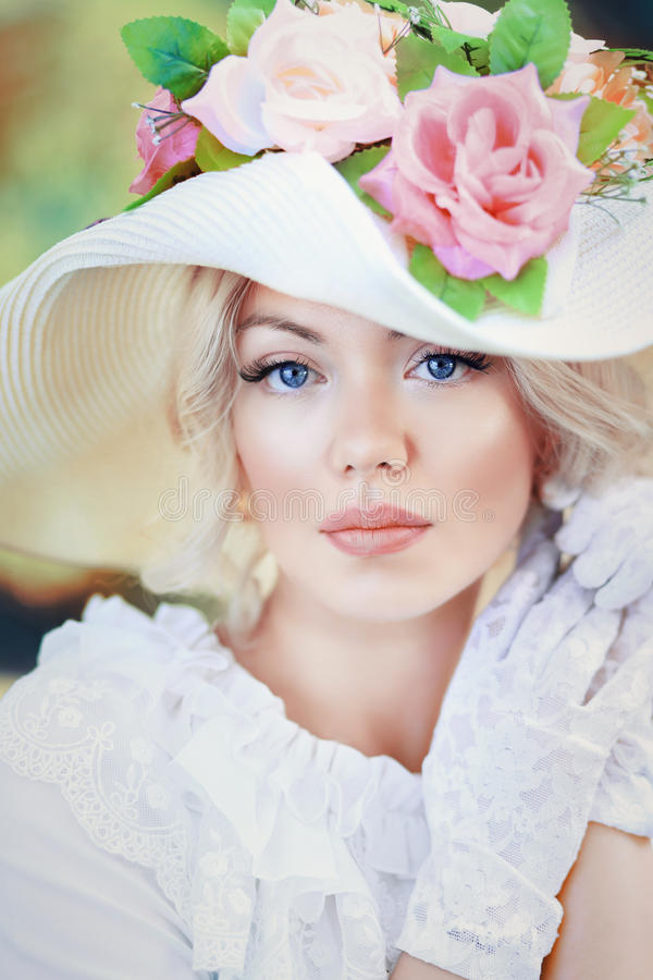 Woman in victorian age. Portrait of beautiful woman in victorian age dress and fancy hat with flowers royalty free stock photos