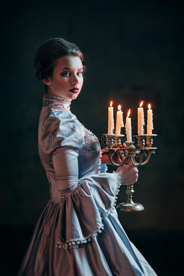 Woman in victorian dress. Imprisoned in a dungeon stock photography