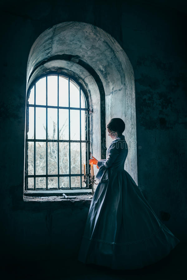 Woman in victorian dress. Imprisoned in a dungeon stock photos