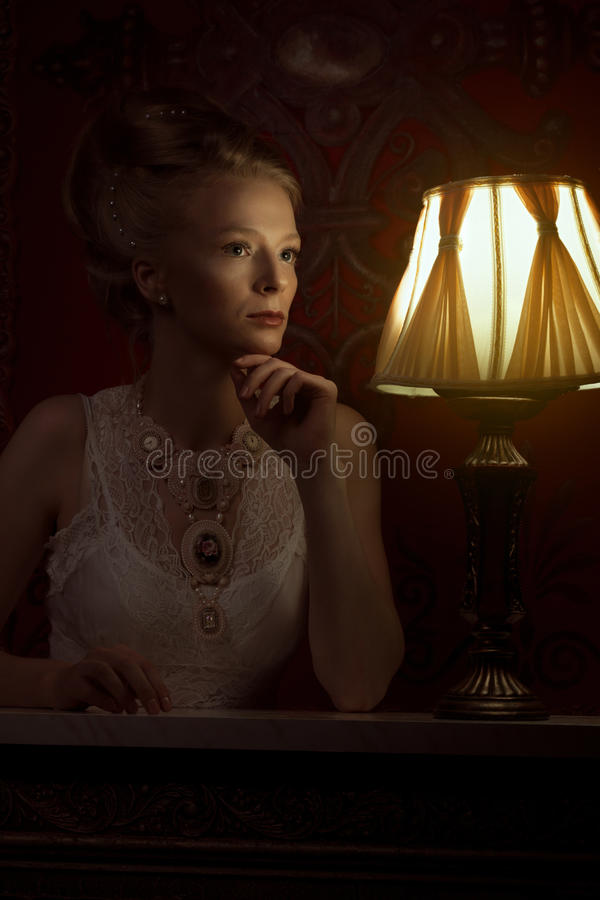 Woman in victorian style and vintage room with lamp beside her royalty free stock image