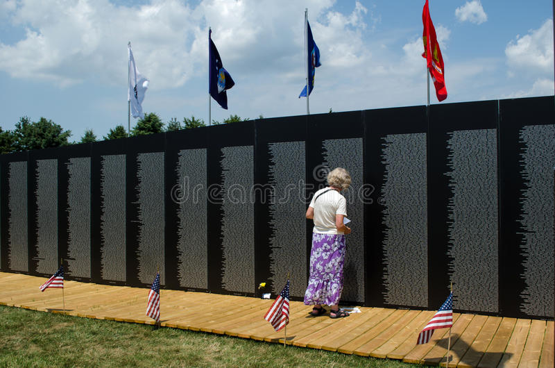 Woman at the vietnam wall memorial. A woman looks over some of 58,000 names of soldiers who died in the vietnam war. this memorial is 360 feet long and 8 feet stock photo