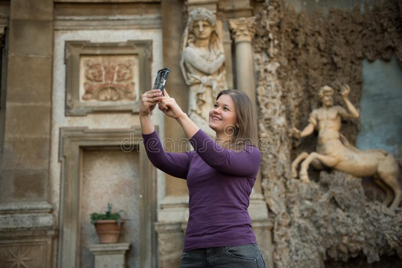 Woman in Villa Aldobrandini, Italy. Young woman in Villa Aldobrandini, Frascati, Italy, in front of antique fontain, maked selfie photos with smartphone stock images
