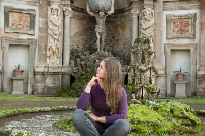 Woman in Villa Aldobrandini, Italy. Young woman in Villa Aldobrandini, Frascati, Italy, in front of antique fontain, sitting stock photography