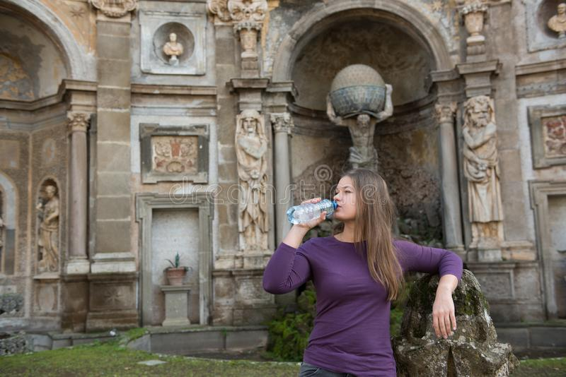 Woman in Villa Aldobrandini, Italy. Young woman in Villa Aldobrandini, Frascati, Italy, in front of antique fontain, drinking water stock photos