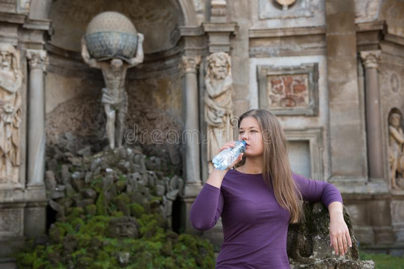 Woman in Villa Aldobrandini, Italy. Young woman in Villa Aldobrandini, Frascati, Italy, in front of antique fontain, drinking water royalty free stock photo