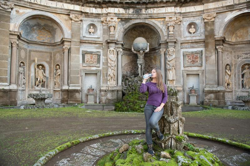 Woman in Villa Aldobrandini, Italy. Young woman in Villa Aldobrandini, Frascati, Italy, in front of antique fontain, drinking water royalty free stock photography