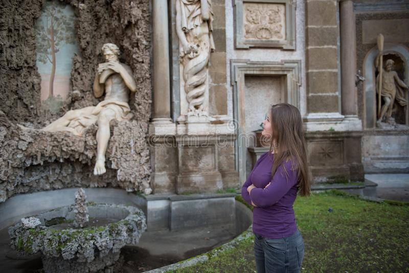Woman in Villa Aldobrandini, Italy. Young woman in Villa Aldobrandini, Frascati, Italy, in front of antique fontain. looking at statue royalty free stock photo