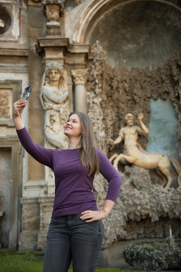 Woman in Villa Aldobrandini, Italy. Young woman in Villa Aldobrandini, Frascati, Italy, in front of antique fontain, maked selfie photos with smartphone stock photo