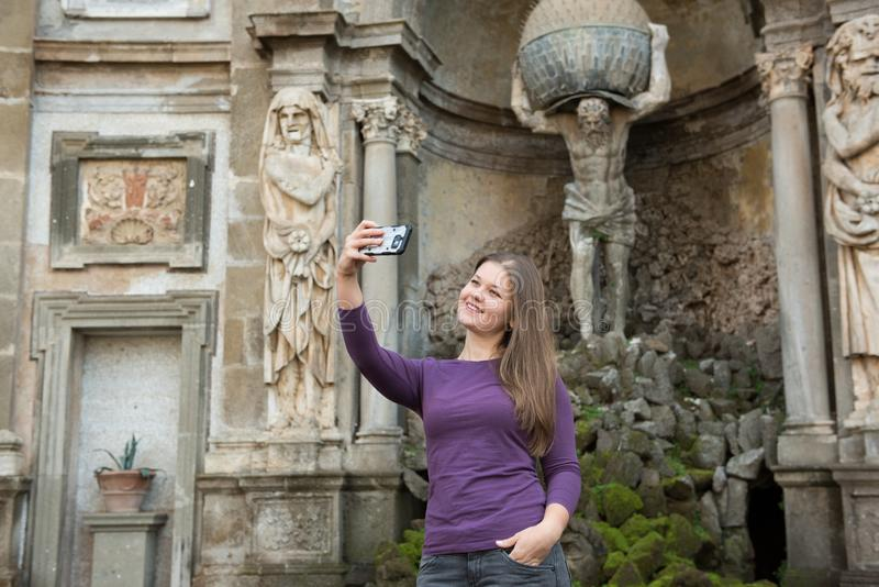 Woman in Villa Aldobrandini, Italy. Young woman in Villa Aldobrandini, Frascati, Italy, in front of antique fontain, maked selfie photos with smartphone royalty free stock images