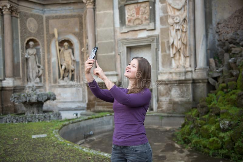 Woman in Villa Aldobrandini, Italy. Young woman in Villa Aldobrandini, Frascati, Italy, in front of antique fontain, maked selfie photos with smartphone royalty free stock image