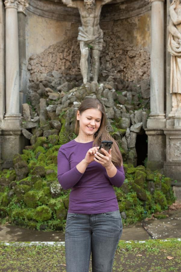 Woman in Villa Aldobrandini, Italy. Young woman in Villa Aldobrandini, Frascati, Italy, in front of antique fontain, texting with smartphone royalty free stock photography