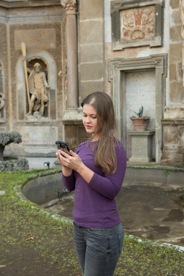 Woman in Villa Aldobrandini, Italy. Young woman in Villa Aldobrandini, Frascati, Italy, in front of antique fontain, texting with smartphone stock image