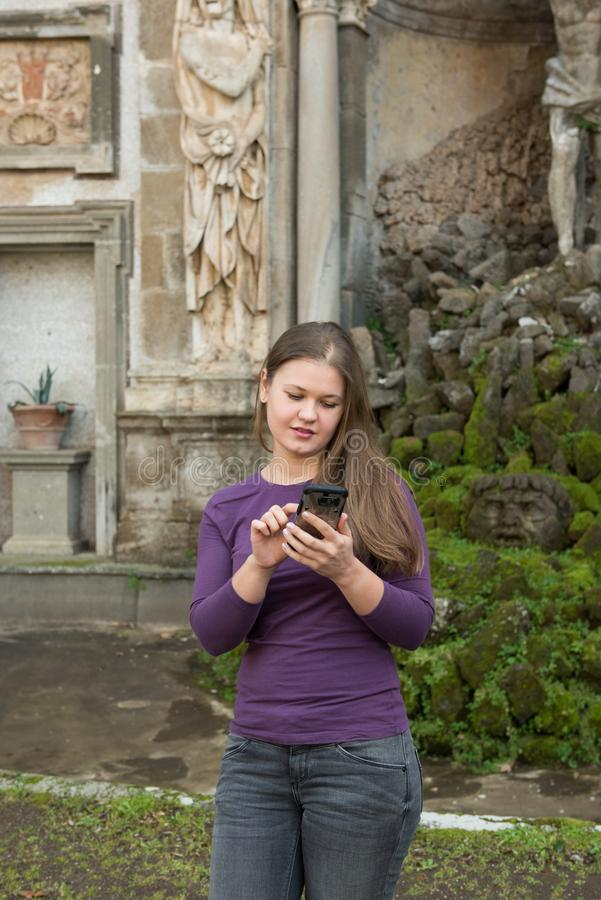 Woman in Villa Aldobrandini, Italy. Young woman in Villa Aldobrandini, Frascati, Italy, in front of antique fontain, texting with smartphone royalty free stock image