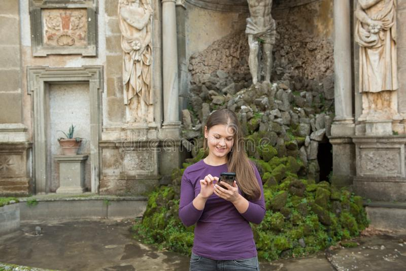 Woman in Villa Aldobrandini, Italy. Young woman in Villa Aldobrandini, Frascati, Italy, in front of antique fontain, texting with smartphone stock photo