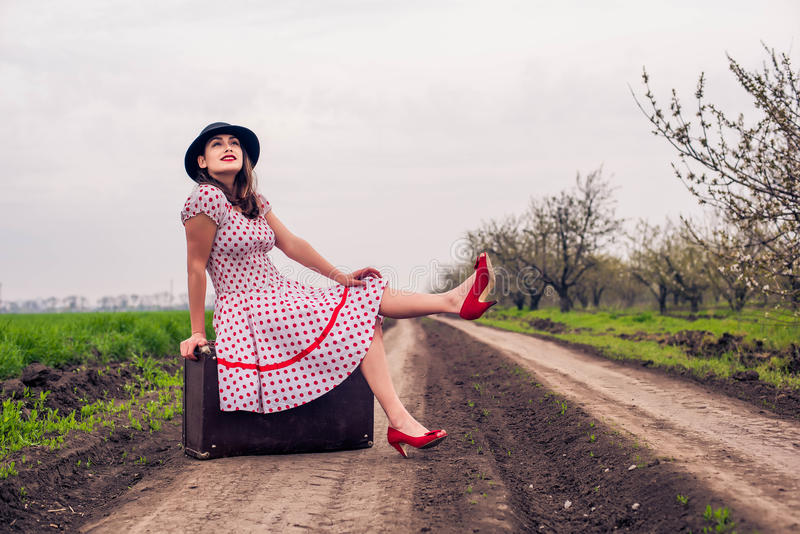 Woman in vintage clothes with suitcase. In field. Vintage toning stock photography