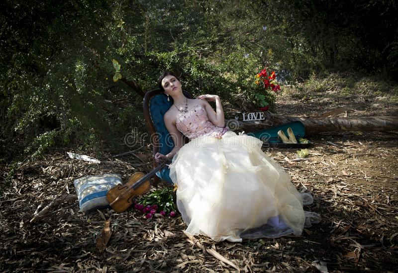 Woman in vintage couture dress reclining on rococo chair amidst an enchanted forest. Color portrait of a gorgeous brunette woman wearing a vintage couture stock photos