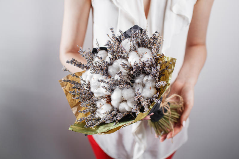 Woman in vintage dress holding bunch of lavender cotton in her hands royalty free stock photo
