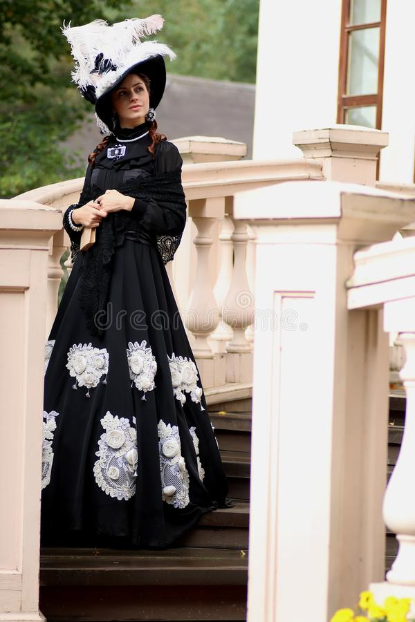 Woman in vintage dress on porch of castle stock photo