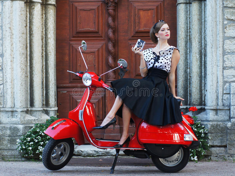 A woman in a vintage dress sitting on a scooter. A young and attractive brunette Caucasian woman in a vintage dress sitting on a red retro scooter. The image is royalty free stock image