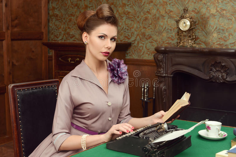 Woman in vintage interior prints on an old typewriter. Pin-up beautiful young woman 50s American style in vintage interior stock images