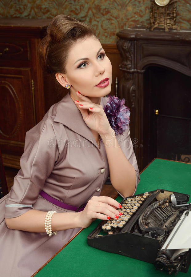 Woman in vintage interior prints on an old typewriter. Pin-up beautiful young woman 50s American style in vintage interior royalty free stock photo