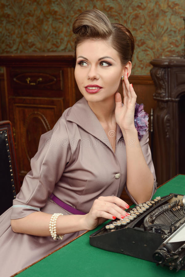 Woman in vintage interior prints on an old typewriter. Pin-up beautiful young woman 50s American style in vintage interior royalty free stock photography