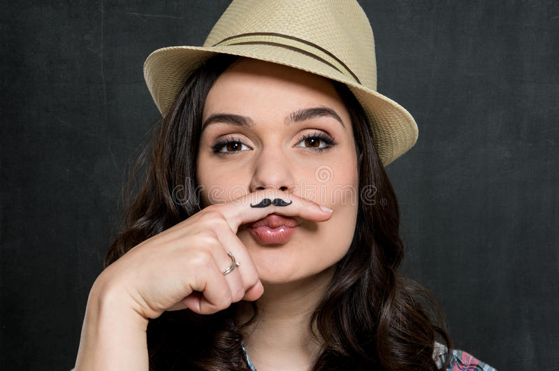 Woman With Vintage Moustache. Portrait Of Young Woman In Hat With Painted Moustache Over Gray Background royalty free stock photography