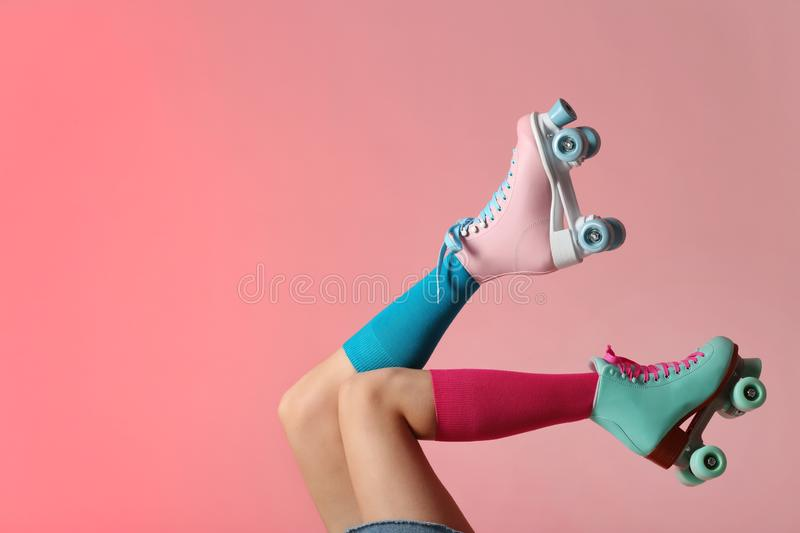 Woman with vintage roller skates on color background royalty free stock images