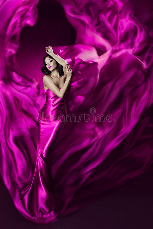 Woman in violet waving silk dress as flame. Woman in purple silk dress waving on wind, girl dancing in flying flame satin cloth stock image
