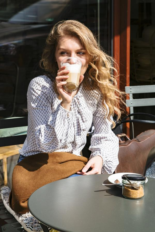 Woman violinist drinks coffee sitting in city cafe royalty free stock photo