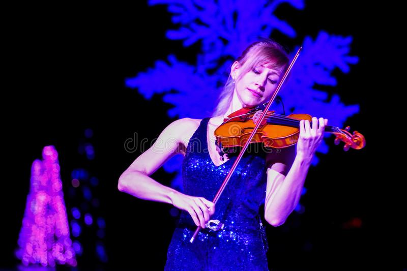 Woman violinist playing holiday music on Christmas Celebration at SeaWorld 2. stock images
