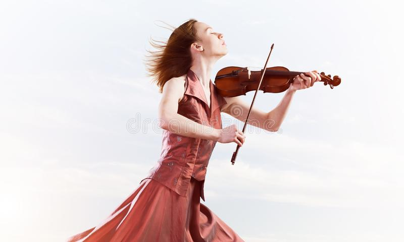 Woman violinist in red dress playing melody against cloudy sky. Young attractive girl playing violin over blue sky and cloud stock image