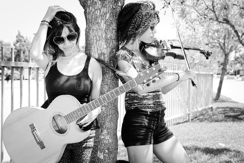 Woman violinist and woman guitarist leaning against tree. High key black and white portrait of Filipino female guitarist and biracial African American violinist