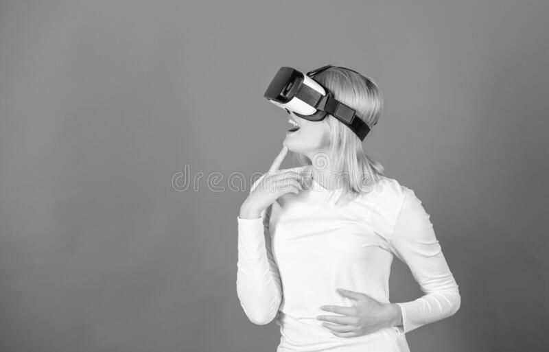 Woman with virtual reality headset. Happy young woman wearing virtual reality goggles watching movies or playing video royalty free stock image