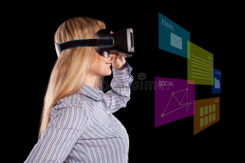 Woman in virtual reality headset. Profile view of intrigued woman in grey shirt wearing virtual reality 3D headset and exploring the play on black background stock images