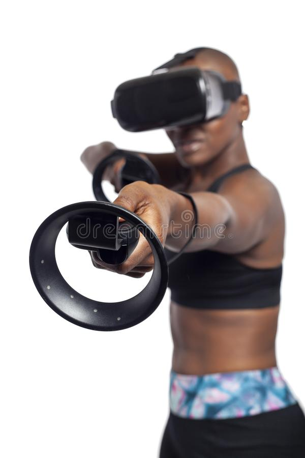 Woman in Virtual Reality Holding VR Wands or Controllers. Black female gamer holding virtual reality controllers or wands and wearing a VR headset.  She is stock photos