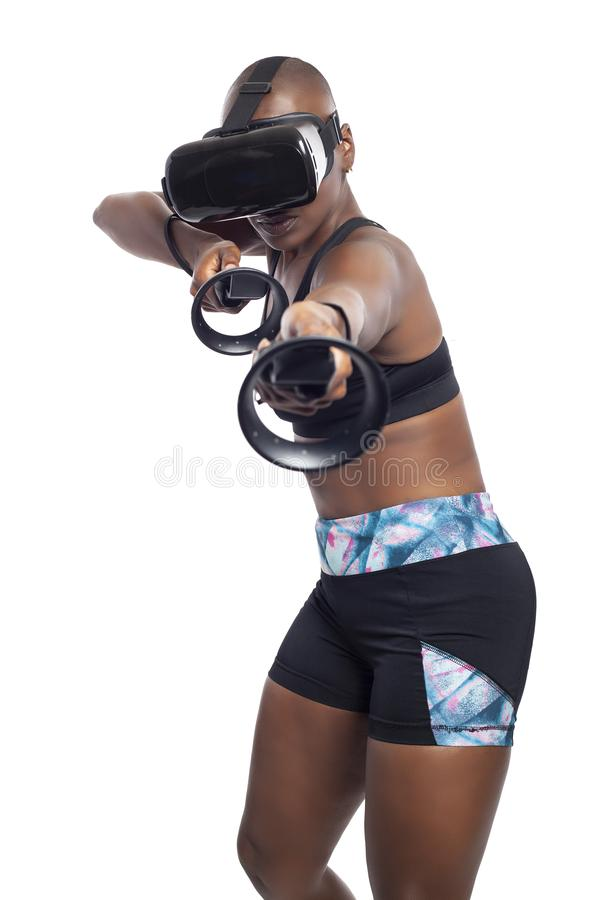 Woman in Virtual Reality Holding VR Wands or Controllers. Black female gamer holding virtual reality controllers or wands and wearing a VR headset.  She is royalty free stock photography