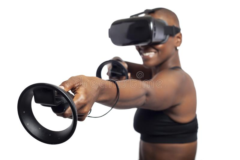 Woman in Virtual Reality Holding VR Wands or Controllers. Black female gamer holding virtual reality controllers or wands and wearing a VR headset.  She is royalty free stock image