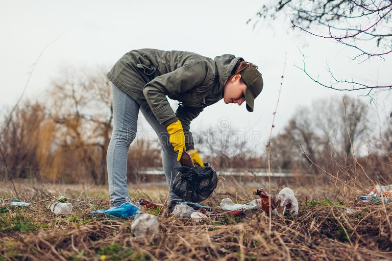 Woman volunteer cleaning up the trash in park. Picking up garbage outdoors. Ecology and environment concept stock image