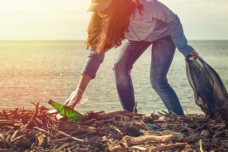 Woman volunteer helps clean the beach of garbage. Earth day and environmental improvement concept. Ecology and safety for future. Generation concept. Light from stock photography