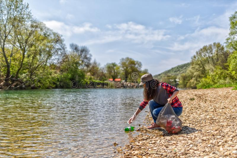 Woman volunteer helps clean the shore of river of garbage. Earth day and environmental improvement concept.  stock images