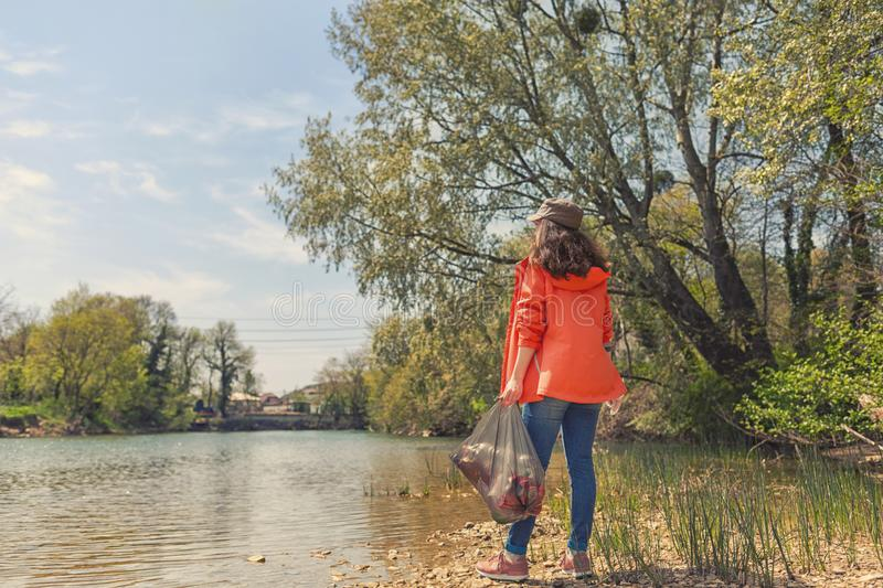 Woman volunteer standing on the river Bank with a bag of garbage. The concept of environmental pollution. Sky, river and trees in royalty free stock image