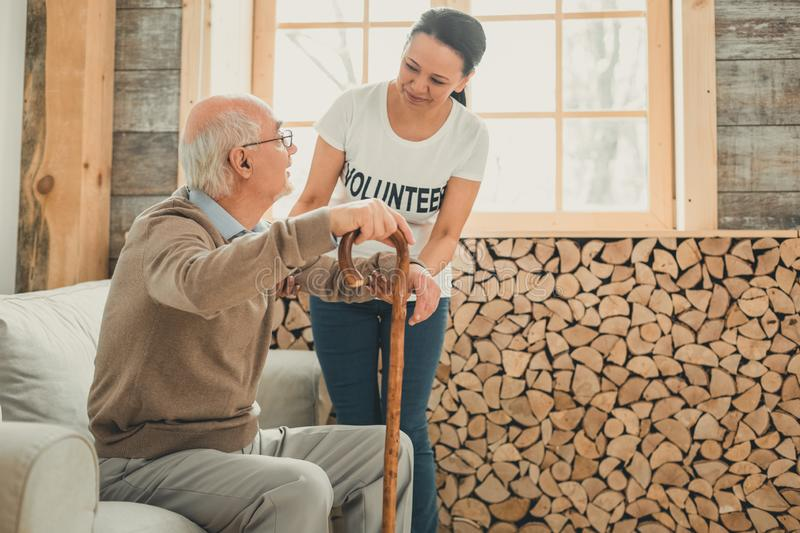 Woman volunteer supporting old man rising from sofa. Act of help. Woman volunteer supporting old men rising from sofa while he carrying wooden stick in one hand stock image