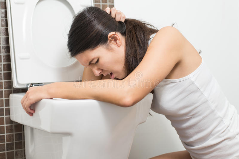 Woman vomiting into the toilet bowl. Young woman vomiting into the toilet bowl in the early stages of pregnancy or after a night of partying and drinking stock image
