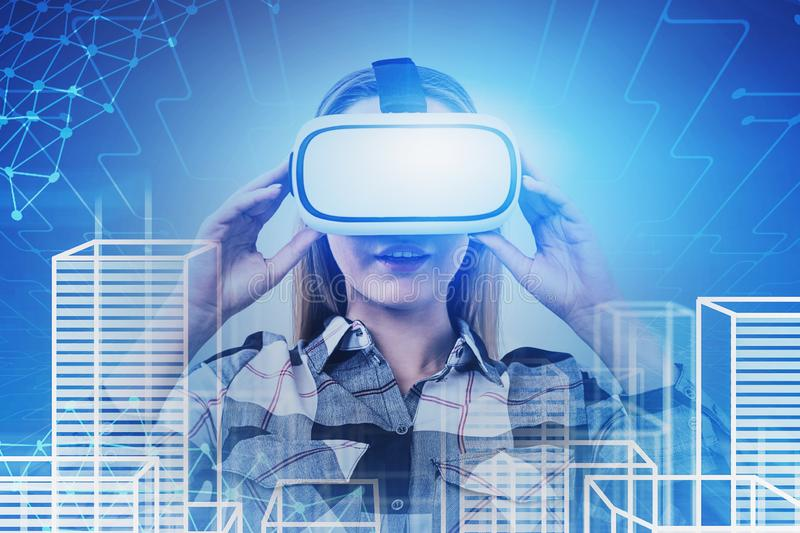 Woman in VR glasses in smart city, internet. Astonished blonde young woman in VR glasses looking at virtual city with network interface. Concept of hi tech and royalty free stock photos