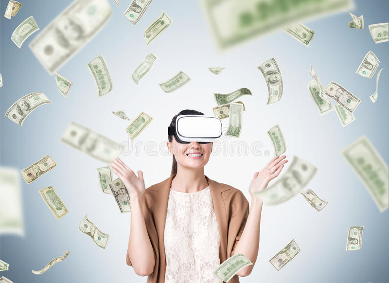 Woman in vr glasses under dollar rain stock images
